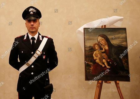 """Italian Carabinieri paramilitary police officer stands next to the 15th century painting """"Madonna with Child"""", attributed to Renaissance painter Cima da Conegliano (Gian Battista Cima), during a press conference on recovered paintings seized by the Nazis in 1944 in Camaiore near Lucca, Italy, at the Brera Art Gallery, in Milan, Italy, . The paintings were seized from the Italian villa of Prince Felix Bourbon-Parma, then Prince of Luxembourg, and kept by the Supreme Comander of all SS forces Italy Karl Wolff at his residency of the Castle Dornsberg, near Merano, South Tyrol before being sent to Germany. The paintings were found on Dec. 3, 2014 in Milan"""