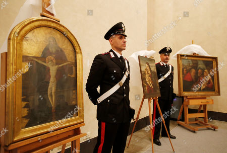 """Italian Carabinieri paramilitary police officers stand next to a painting """"Trinity"""", attributed to early Renaissance painter Alessio Baldovinetti, left, and """"Circumcision of Jesus at Temple"""", attributed to early Renaissance painter Girolamo dai Libri, during a press conference on recovered paintings seized by the Nazis in 1944 in Camaiore near Lucca, Italy, at the Brera Art Gallery, in Milan, Italy, . The paintings were seized from the Italian villa of Prince Felix Bourbon-Parma, then Prince of Luxembourg, and kept by the Supreme Comander of all SS forces Italy Karl Wolff at his residency of the Castle Dornsberg, near Merano, South Tyrol before being sent to Germany. The paintings were found on Dec. 3, 2014 in Milan"""