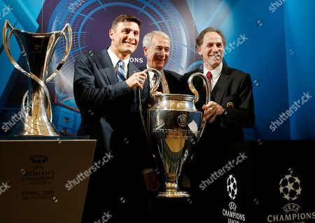 Milan's mayor Giuliano Pisapia holds the trophy with former Inter Milan player Javier Zanetti and former AC Milan player Franco Baresi at the end of the press conference to present the soccer Champions League final, in Milan, Italy, . The final will be held on May 28