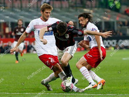 AC Milan's Giacomo Bonaventura, center, tries to dribbles pat Carpi's Simone Romagnoli, left, and Cristian Zaccardo during the Serie A soccer match between AC Milan and Carpi at the San Siro stadium in Milan, Italy