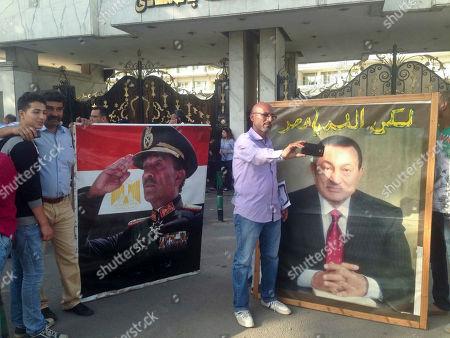 Supporters of Egypt's President Abdel-Fattah el-Sissi pose with posters of ousted leader Hosni Mubarak, right, and Anwar Sadat, left, at a rally in Cairo on . Elsewhere, Police fired tear gas and birdshot to disperse hundreds of demonstrators calling on President Abdel-Fattah el-Sissi to step down over his government's decision to surrender control over two strategic Red Sea islands to Saudi Arabia