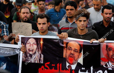 """People chant anti-government slogans during a demonstration against the security forces' failure to protect them from car bombs at the site of yesterday's car bomb attack in the Iraqi capital's eastern district of Sadr City, Iraq, . The protesters hold posters with defaced pictures of Iraq's Interior Minister Mohammed al-Ghabban, right, former Iraqi Prime Minister Nouri al-Maliki, center, and Iraqi lawmaker Hanan al-Fatlawi, left, with Arabic reading, """"leave, leave you failure,"""" and """"your message has been received,"""" and """"No No to terrorism"""