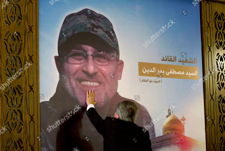 """Adnan Badreddine, brother of top Hezbollah commander Mustafa Badreddine, grieves at his brother's picture in a southern suburb of Beirut, Lebanon, . Lebanon's militant Hezbollah group said Friday that its top military commander who was supervising its military operations in Syria, Mustafa Badreddine, was killed in an explosion in Damascus, a major blow to the Shiite group which has played a significant role in the conflict next door. Words in Arabic say """"The martyr commander Mustafa Badreddine"""