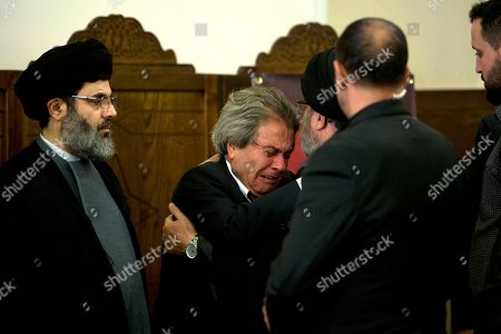 Adnan Badreddine, center, brother of top Hezbollah commander Mustafa Badreddine, cries as he receives condolences from Hezbollah senior officials in a southern suburb of Beirut, Lebanon, . Lebanon's militant Hezbollah group said Friday that its top military commander who was supervising its military operations in Syria, Mustafa Badreddine, was killed in an explosion in Damascus, a major blow to the Shiite group which has played a significant role in the conflict next door