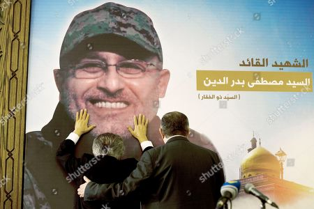 """Adnan Badreddine, left, brother of top Hezbollah commander Mustafa Badreddine, grieves at his brother's picture in a southern suburb of Beirut, Lebanon, . Lebanon's militant Hezbollah group said Friday that its top military commander who was supervising its military operations in Syria, Mustafa Badreddine, was killed in an explosion in Damascus, a major blow to the Shiite group which has played a significant role in the conflict next door. Words in Arabic say """"The martyr commander Mustafa Badreddine"""