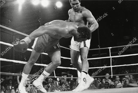 Challenger Muhammad Ali watches as defending world champion George Foreman goes down to the canvas in the eighth round of their WBA/WBC championship match in Kinshasa, Zaire. Ali, the magnificent heavyweight champion whose fast fists and irrepressible personality transcended sports and captivated the world, has died according to a statement released by his family . He was 74