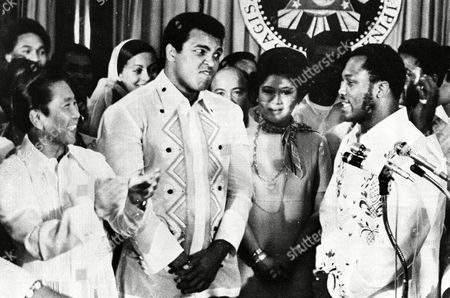 Philippines President Ferdinand Marcos, left, applauds as challenger Joe Frazier, right, makes some remarks about world champion Muhammad Ali, second from left, during their call on Marcos at the Malacanang Palace in Manila, Philippines. Ali, the magnificent heavyweight champion whose fast fists and irrepressible personality transcended sports and captivated the world, has died according to a statement released by his family . He was 74