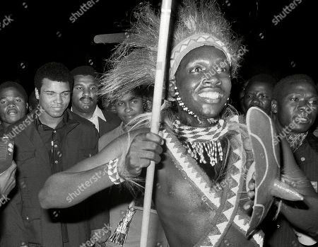 A Zairian man in traditional clothing carries a spear as he leads Muhammad Ali through a crowd at the airport in Kinshasa, Zaire. Ali arrived in a chartered Air Zaire plane from Paris for a world championship fight with George Foreman. Ali, the magnificent heavyweight champion whose fast fists and irrepressible personality transcended sports and captivated the world, has died according to a statement released by his family . He was 74