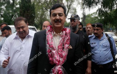 Pakistan's former Prime Minister Yusuf Raza Gilani, center, is greeted by supporters upon arrival at his residence in Islamabad, Pakistan, . A joint raid by U.S. and Afghan forces on Tuesday his son who was held captive for three years by Islamic militants, officials said. Ali Haider Gilani was found during the raid near Afghanistan's eastern border with Pakistan, according to a spokesman for Afghan President Ashraf Ghani