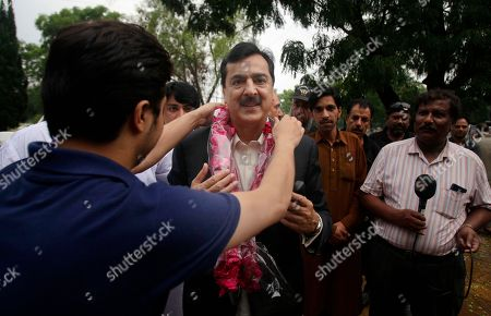 Pakistan's former Prime Minister Yusuf Raza Gilani, center, is greeted by supporters upon arrival at his residence in Islamabad, Pakistan, . A joint raid by U.S. and Afghan forces on Tuesday rescued the son of a former Pakistani prime minister who was held captive for three years by Islamic militants, officials said. Ali Haider Gilani was found during the raid near Afghanistan's eastern border with Pakistan, according to a spokesman for Afghan President Ashraf Ghani