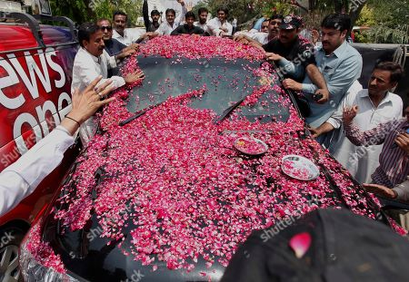 Stock Image of Supporters shower rose-petals on a vehicle carrying Ali Haidar Gilani, son of former Pakistani Prime Minister Yusuf Raza Gilani upon arrival at his residence in Lahore, Pakistan, . Gilani, the son of a former Pakistani prime minister who was freed from kidnappers in a dramatic military rescue in Afghanistan arrived back home Wednesday and reunited with family, officials and family members said