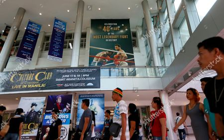 "People walk past the huge billboard heralding the 1975 ""Thrilla-in-Manila"" heavyweight boxing fight between Muhammad Ali and Joe Frazier at the exact venue at the Araneta Coliseum now renamed as Smart Araneta Coliseum, in Quezon city, northeast of Manila, Philippines. From Manny Pacquiao to left-wing activists, Filipinos in this boxing-crazy nation on Saturday grieved the death of Muhammad Ali, which brought back fond memories of the epic fight"