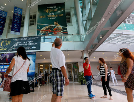 "A man points to the huge billboard heralding the 1975 ""Thrilla-in-Manila"" heavyweight boxing fight between Muhammad Ali and Joe Frazier at the exact venue at the Araneta Coliseum now renamed as Smart Araneta Coliseum, in Quezon city, northeast of Manila, Philippines. From Manny Pacquiao to left-wing activists, Filipinos in this boxing-crazy nation on Saturday grieved the death of Muhammad Ali, which brought back fond memories of the epic fight"