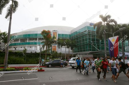 "People cross the street with the Smart Araneta Coliseum in the background at Cubao in suburban Quezon city, northeast of Manila, Philippines. The ""Big Dome"" was the exact venue 40 years ago of the epic 1975 ""Thrilla in Manila"" heavyweight boxing bout between Muhammad Ali and Joe Frazier which the former won via a TKO in the 15th round. Ali, the magnificent heavyweight champion whose fast fists and irrepressible personality transcended sports and captivated the world, died according to a statement released Friday by his family. He was 74"