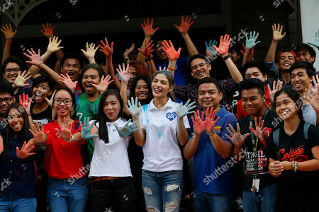 "Lovi Poe Actress Lovi Poe, center, the sister of Presidential candidate Grace Poe displays her color-stained hands as she joins students in a symbolic throwing of colored powder to endorse ""Kabataan"" party list group, a youth organization trying to campaign for a seating the Lower House, at suburban Quezon city northeast of Manila, Philippines. Poe is running second to front-running candidate Rodrigo Duterte in recent poll surveys leading to Monday's Presidential elections"