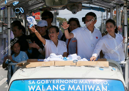 "Grace Poe, Heart Evangelista Escudero, Francis ""Chiz"" Escudero Presidential candidate Sen. Grace Poe and her running mate Sen. Francis ""Chiz"" Escudero, throw souvenir t-shirts and rubber wrist bands as their motorcade makes the rounds of townships in Rizal province east of Manila, Philippines . Poe is running second to front runner Rodrigo Duterte in recent poll ahead of the May 9 presidential elections. At right is Escudero's wife Heart Evangelista Escudero"