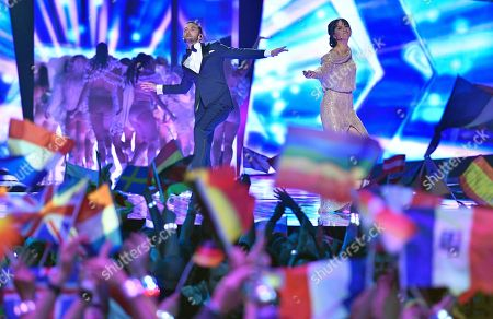 Hosts Mans Zelmerlow and Petra Mede dance as they arrive for the Eurovision Song Contest final in Stockholm, Sweden