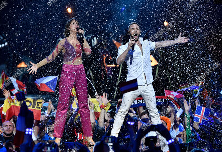 Swedish hosts Mans Zelmerlow and Petra Mede, left, sing a song during the Eurovision Song Contest final in Stockholm, Sweden