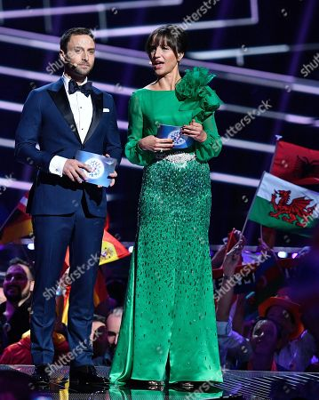 Hosts Mans Zelmerlow and Petra Mede talk as they wait for the start of the voting during the Eurovision Song Contest final in Stockholm, Sweden