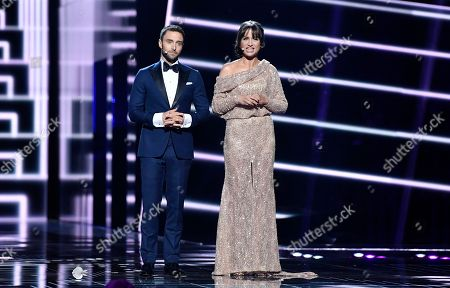 Stock Picture of Swedish hosts Mans Zelmerlow and Petra Mede, right, stand on the stage during the Eurovision Song Contest final in Stockholm, Sweden