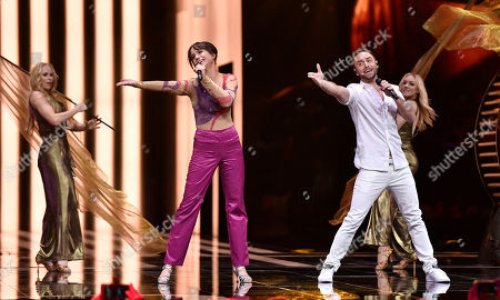 Swedish hosts Mans Zelmerlow, right, and Petra Mede sing a song during the Eurovision Song Contest final in Stockholm, Sweden