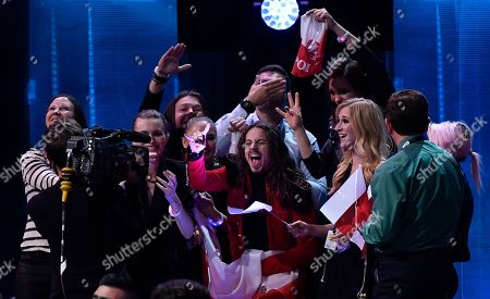 Poland's Michal Szpak, center, celebrates as he learns the results during the Eurovision Song Contest final in Stockholm, Sweden