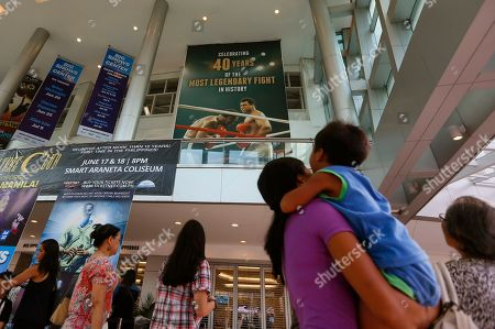 "People look at the huge billboard heralding the epic 1975 ""Thrilla in Manila"" heavyweight boxing bout between Muhammad Ali and Joe Frazier at the exact venue 40 years ago at the Araneta Coliseum which is now renamed as Smart Araneta Coliseum in Cubao in suburban Quezon city, northeast of Manila, Philippines. Ali, the magnificent heavyweight champion whose fast fists and irrepressible personality transcended sports and captivated the world, died according to a statement released Friday by his family. He was 74"
