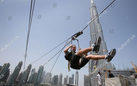 In this April 9, 2016 photo, with the world's tallest tower, Burj Khalifa, in backdrop, a man enjoys an urban zip line attraction in Dubai, United Arab Emirates, . In the air travel hub of Dubai, there's a new way to fly: A zip line run by extreme sports company XDubai. XDubai, which began its operations in 2015, and is associated with Sheikh Hamdan bin Mohammed bin Rashid Al Maktoum, the crown prince of Dubai