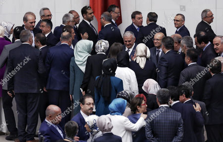 Turkey's new Prime Minister Binali Yildirim, rear center with gray hair, receives congratulations after legislators voted 315-138 to approve his government, in Ankara, Turkey, . Turkey's new government, led by President Recep Tayyip Erdogan's loyal ally, has easily won a vote of confidence in parliament. Yildirim, 60, replaced former premier Ahmet Davutoglu, who stepped down after falling out of favor with Erdogan over a range of issues