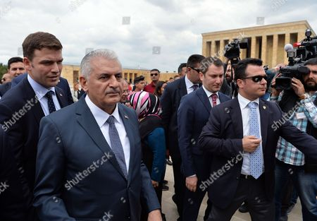 Turkey's new Prime Minister Binali Yildirim, second left, visits the mausoleum of modern Turkey's founder, Mustafa Kemal Ataturk, after legislators voted 315-138 to approve his government, in Ankara, Turkey, . Turkey's new government, led by President Recep Tayyip Erdogan's loyal ally, has easily won a vote of confidence in parliament. Yildirim, 60, replaced former premier Ahmet Davutoglu, who stepped down after falling out of favor with Erdogan over a range of issues