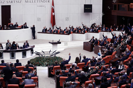 Turkey's new Prime Minister Binali Yildirim, rear, his minister and ruling party legislators vote to approve his government, in Ankara, Turkey, . Turkey's new government, led by President Recep Tayyip Erdogan's loyal ally, has easily won a vote of confidence in parliament. Yildirim, 60, replaced former premier Ahmet Davutoglu, who stepped down after falling out of favor with Erdogan over a range of issues