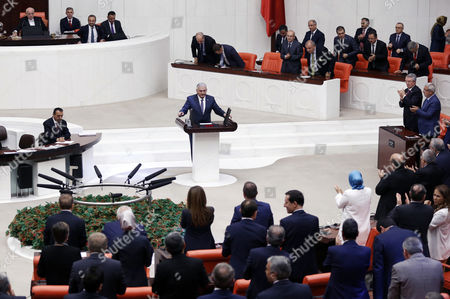 Turkey's new Prime Minister Binali Yildirim addresses the parliament after legislators voted 315-138 to approve his government, in Ankara, Turkey, . Turkey's new government, led by President Recep Tayyip Erdogan's loyal ally, has easily won a vote of confidence in parliament. Yildirim, 60, replaced former premier Ahmet Davutoglu, who stepped down after falling out of favor with Erdogan over a range of issues