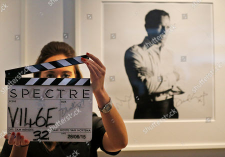Stock Photo of A Christie's employee shows a clapper board for the latest James Bond, Spectre movie at the auction house Christie's in London, . The board is one of the 24 items of Spectre memorabilia that come directly from the archives of EON Productions, with unique donations from Daniel Craig, Sam Mendes, Michael G. Wilson, Barbara Broccoli, Jesper Christensen and Sam Smith an it's auction on February 15, 2016. An online-only sale will offer 14 lots and open for bidding from Tuesday Feb. 16, 2016. The estimate of the clapper board is 2,000-3,000 GBP, (2,800-4,300 USD