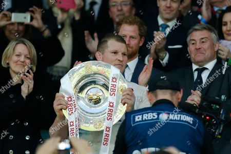 Prince Harry applauds behind England captain Dylan Hartley holding the Triple Crown trophy for defeating the other three home nations after the Six Nations international rugby match between England and Wales at Twickenham stadium in London, Saturday, March,12, 2016. England won 25-21