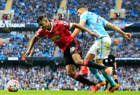 United's Marcus Rashford, left, and Manchester City's Martin Demichelis challenge for the ball during the English Premier League soccer match between Manchester City and Manchester United at the Etihad stadium in Manchester