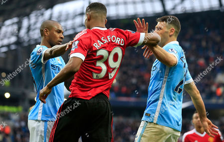 Manchester City's Fernandinho, left, Manchester City's Martin Demichelis, right, and United's Marcus Rashford argue during the English Premier League soccer match between Manchester City and Manchester United at the Etihad stadium in Manchester