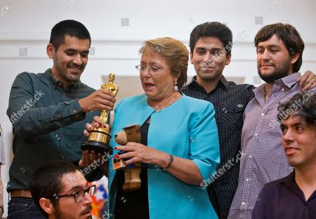 Gabriel Osorio, director of the Oscar winning animated short film Bear Story, left, shows his Oscar statue to Chile's President Michelle Bachelet during a media event at La Moneda palace in Santiago, Chile, . The film was inspired by the story of Osorio's grandfather who was taken prisoner after Chile's military coup in 1973 and lived in exile during Augusto Pinochet's dictatorship