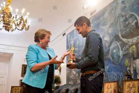 Chile's President Michelle Bachelet meets with Gabriel Osorio who holds his Oscar for animated short film Bear Story at La Moneda palace in Santiago, Chile, . The film was inspired by the story of Osorio's grandfather who was taken prisoner after Chile's military coup in 1973 and lived in exile during Augusto Pinochet's dictatorship