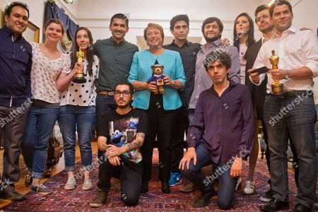 Chile's President Michelle Bachelet, center, poses for photos the makers of Oscar winning animated short film Bear Story at La Moneda palace in Santiago, Chile, Tuesday, 1, March, 2016. The directors are Gabriel Osorio, fourth from left, and Pato Escala, far right. The film was inspired by the story of Osorio's grandfather who was taken prisoner after Chile's military coup in 1973 and lived in exile during Augusto Pinochet's dictatorship