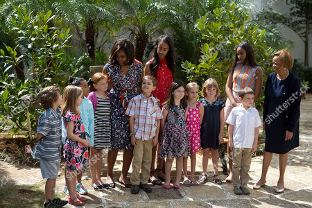"""Michelle Obama, Malia Obama, Sasha Obama, Marian Robinson U.S. First Lady Michelle Obama, center left, talks with children of embassy workers as she poses for a picture along with her daughters Malia, center right, Sasha, second right, and her mother Marian Robinson, left, after dedicating two magnolia trees and a bench, at a small park beside Ruben Martinez Villena public library in Plaza de las Armas, Old Havana, Cuba, . The bench bears the inscription in English and Spanish """"A gift to the people of Cuba from Mrs. Michelle Obama, first lady of the U.S., March 2016"""