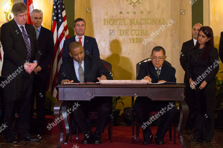 United States Transportation Secretary Anthony Foxx, left, and Cuba's Minister of Transportation Adel Yzquierdo Rodriguez, right, sign an airline transportation agreement as United States Assistant Secretary of State for Economic and Business Affairs Charles Rivkin, behind Foxx, looks on in Havana, Cuba, . The United States and Cuba have signed an agreement to resume commercial air traffic for the first time in five decades