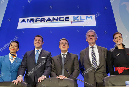 Air France-KLM's Chairman and Chief Executive Officer Alexandre de Juniac, center, KLM's President and Chief Executive Officer Pieter Elbers, right, and Air France's Chairman and Chief Executive Officer Federic Gagey pose with flight attendants prior to the full year 2015 results presentation in Paris, . Air France-KLM Group announced its first annual operating profit since 2010