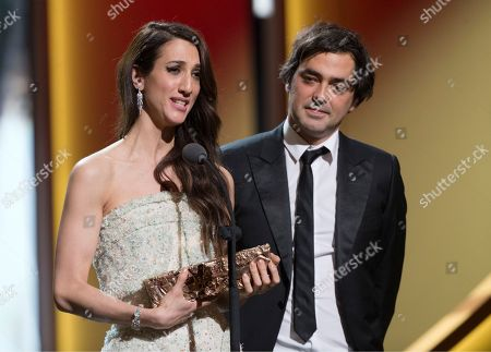 "French producer Charles Gillibert, right, and French-Turkish director Deniz Gamze Erguven celebrate on stage with their trophy after they won the Best First Feature Film award for ""Mustang"" at the ceremony of the 41th Cesar Film Awards at Theatre du Chatelet in Paris, France"