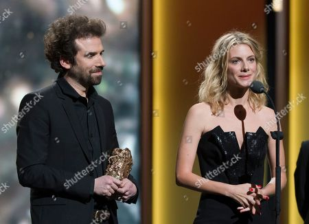 French director Melanie Laurent, right, and French director Cyril Dion celebrate on stage with their trophy after they won the the Best Documentary Feature award for Tomorrow ( Demain) at the ceremony of the 41th Cesar Film Awards at Theatre du Chatelet in Paris, France
