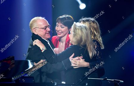 French singer and composer William Sheller, left, embraces singer Jeanne Cherhal, center, Louane and Veronique Sanson after he received a special honour, during the 31st Victoires de la Musique, the annual French music awards ceremony,, in Paris, France