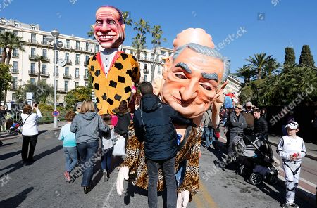 """A revelers carries caricature of businessman Dominique Strauss Kahn, right, close a float showing former italian president and businessman Silvio Berlusconi, during the 132nd Nice carnival parade, in Nice, southeastern France. This year, the Carnival celebrates the """"King of Media"""". (AP Photo/Lionel Cironneau"""