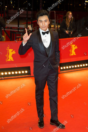 Stock Picture of Actor Qin Hao gestures on the red carpet, prior to the screening of 'Chang Jiang Tu', at the 2016 Berlinale Film Festival in Berlin