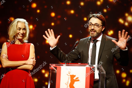 Producer Dora Bouchoucha, left, looks on as Director Mohamed Ben Attia, winner of the Best First Feature Award for his film 'Inhebbek Hedi' speak on stage, during the award ceremony at the 2016 Berlinale Film Festival in Berlin