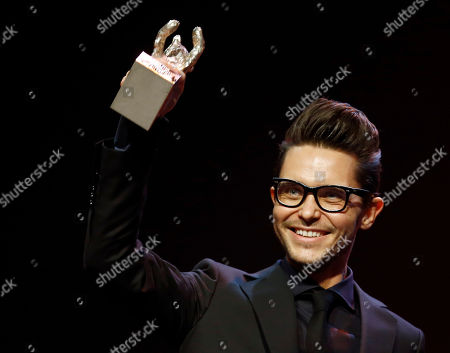 Tomasz Wasilewski gestures with his Silver Bear he received as script writer for 'Zjednoczone Stany Milosci', during the award ceremony at the 2016 Berlinale Film Festival in Berlin