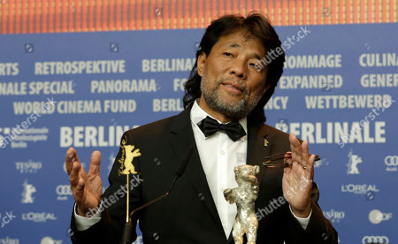 Mark Lee Ping-Bing, cameraman of 'Chang Jiang Tu' sits beside his Silver Bear for Outstanding Artistic Contribution during a press conference after the award ceremony of the 2016 Berlinale Film Festival in Berlin, Germany